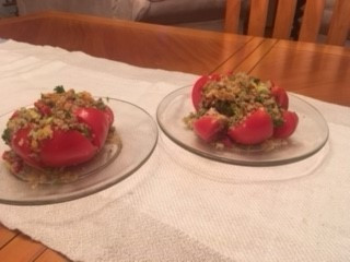 2 plates on a white table cloth, tomatoes stuffed with quinoa and vegetables