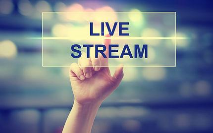 Hand pressing Live Stream on blurred cit