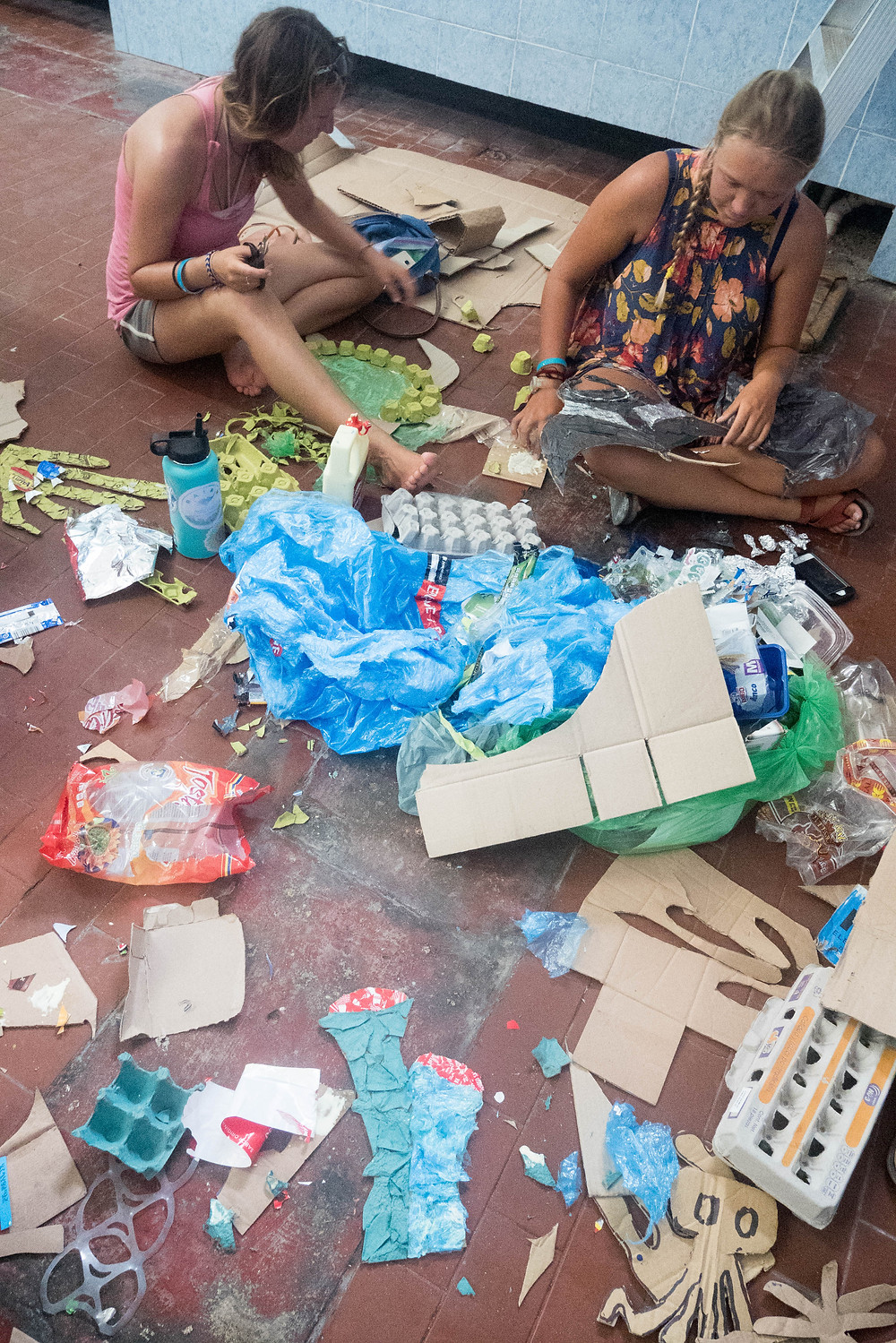 Claudia and Addison working on the mural, surrounded by rubbish.