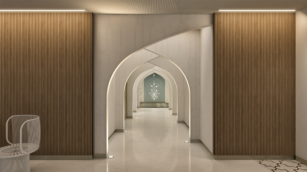 A Section of the pristine white passages feature concealed lightings paired with intersecting arches. These semi-arches lend the corridors not just the visual depth, but also ease of functionality. Wooden fluted panelling on the walls frame the vaulted pathways