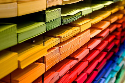 A background image: several colourful pieces of paper all sorted on a shelf