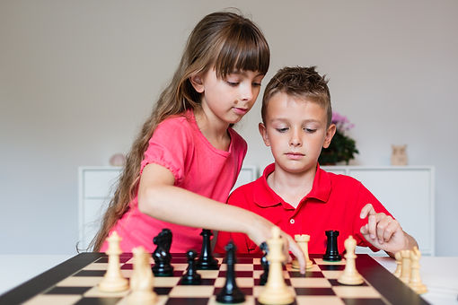 Girl helping boy while playing a game of