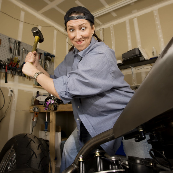 Woman Sledge Sculpting (smashing) a motorcycle with a sledgehammer