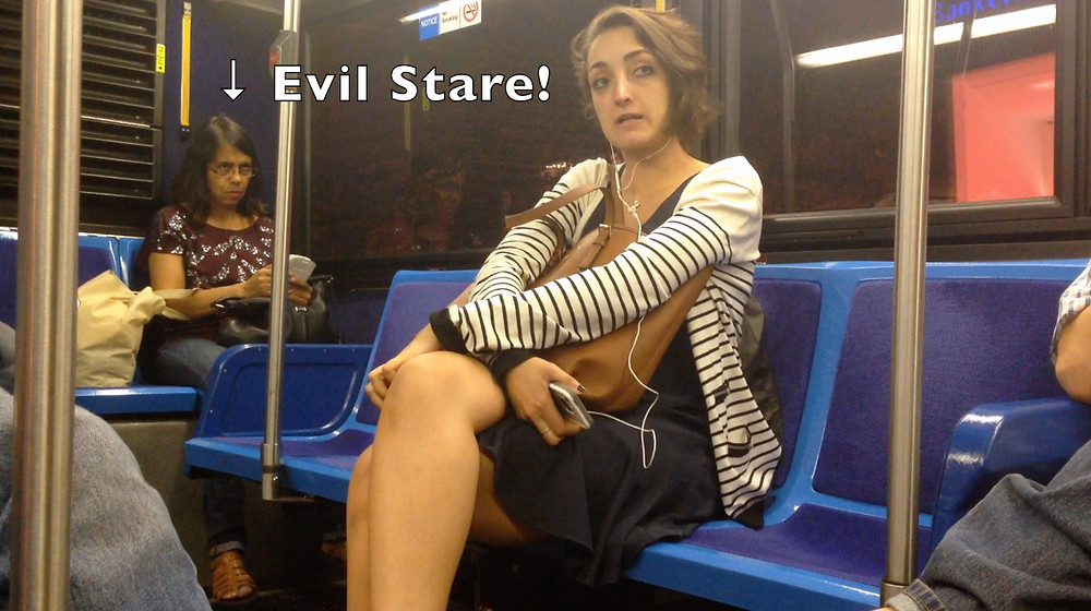 NYC bus, girl speaking loudly on phone receives evil look from a distracted woman trying to read