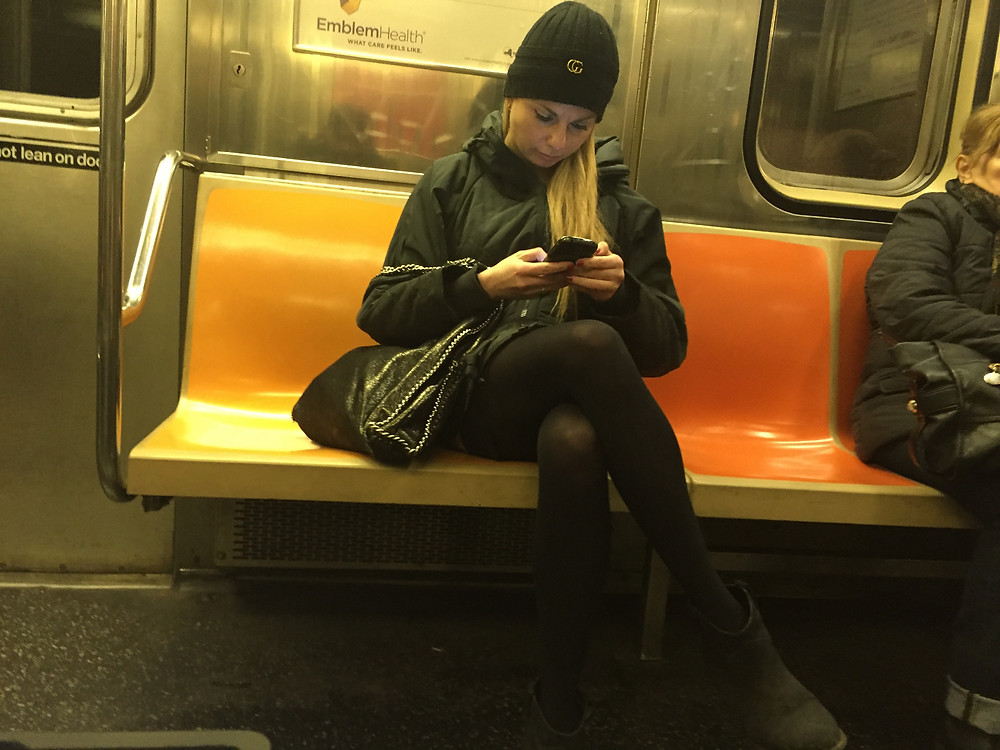 Girl bagspreading, taking up 2 seats on 1 train and blocking aisle with crossed lega
