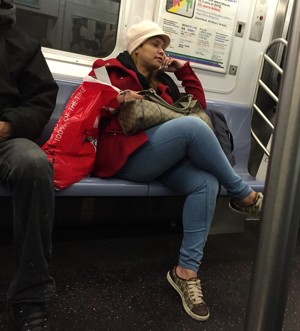 Woman hogging 3 seats with bags, blocks aisle with crossed legs