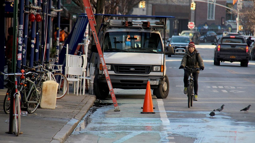 cyclist weaves around a commercial vehicle blocking a bike lane in new york city