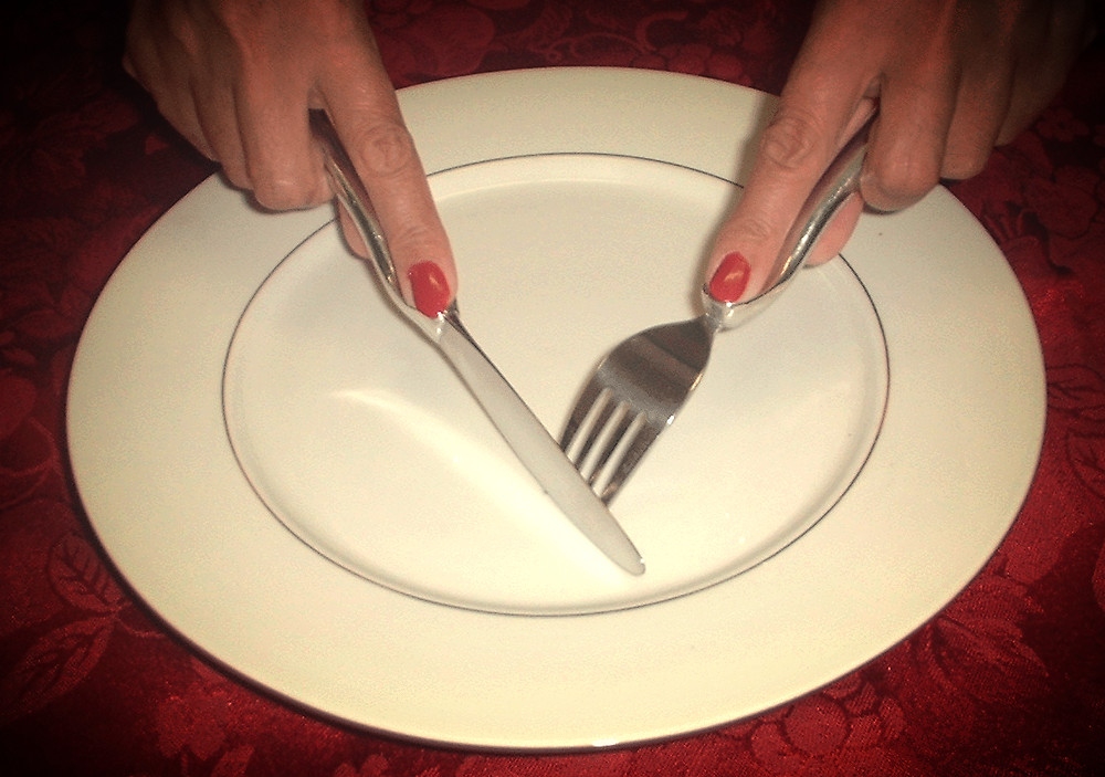 Dining etiquette woman demonstrating how to use a fork and knife properly