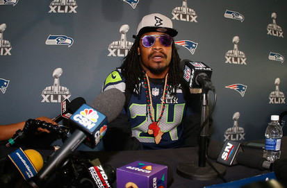 Marshawn Lynch ignoring the questions at a press conference for super bowl XLIX in his beast mode hat