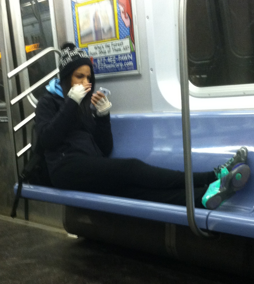 Woman fully extending legs on train seat like it's her couch
