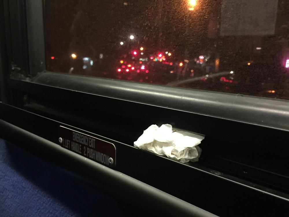 Used kleenex wedged in nyc bus window frame