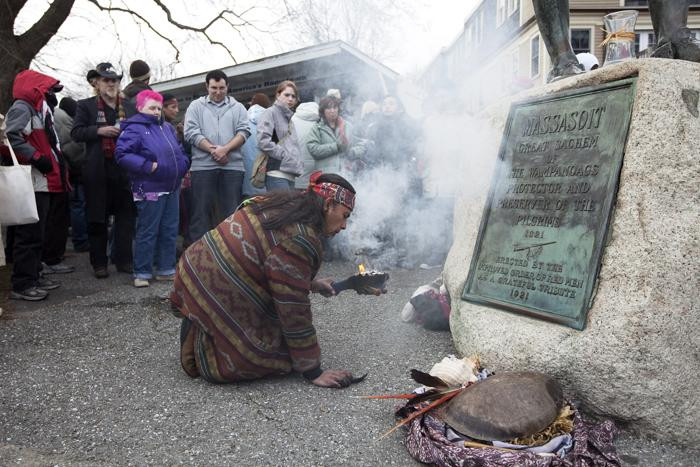 "Juan Gonzalez of Boston rekindles a small fire symbolizing a ritual for healing and a connection with the ""creator"" at the National Day of Mourning in Plymouth on Nov. 25, 2010"
