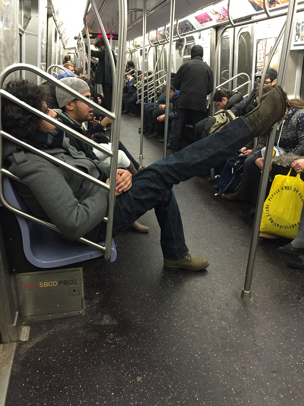 Rude guy relaxing with foot up on the subway pole, blocking people from passing