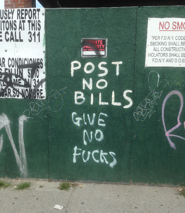"""On construction wall in nyc, under """"post no bills,"""" """"give no fucks is spray painted"""
