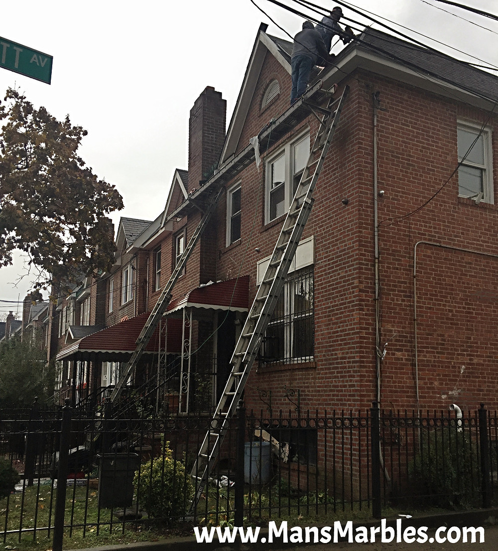 2 unsafe unsafe roofing workers standing a ladder resting on 2 different ladders