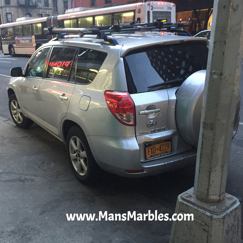 NYC driver parks with one wheel on the sidewalk