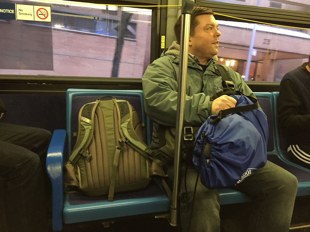 Man bagspreads his backpack on bus in NYC
