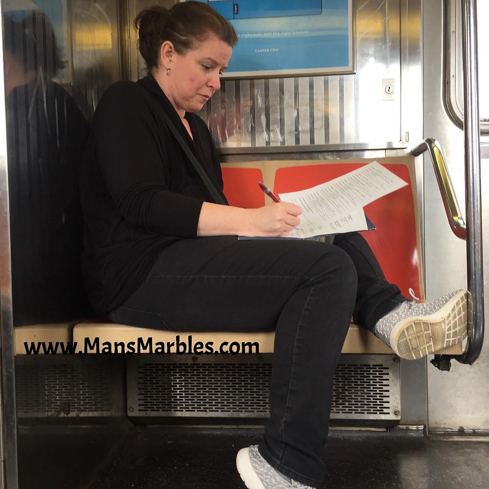 Woman hogging 2 train seats while doing homework