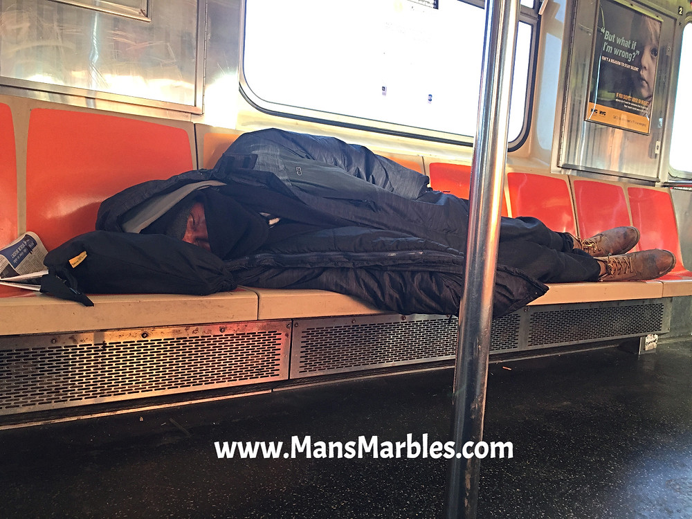 Man taking a nap on 6 train seats in NYC