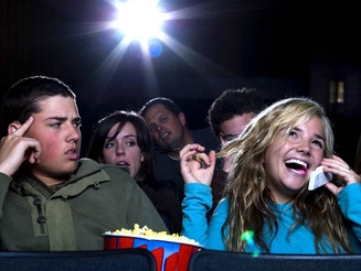 Rude girl talks on cell phone at the movies