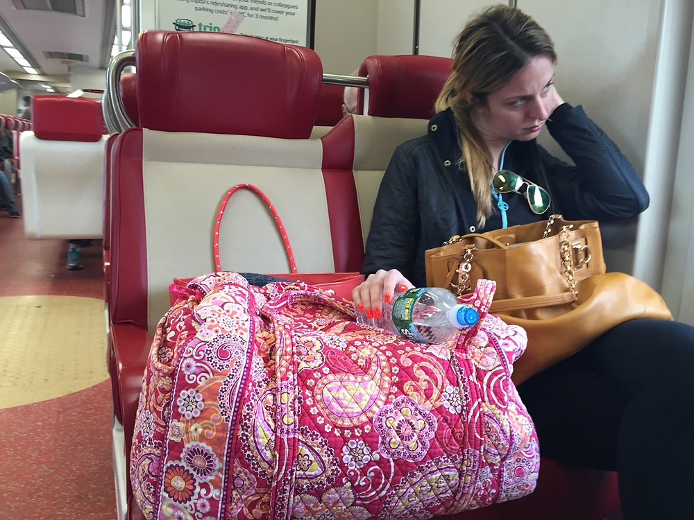 Womanspreading multiple bags on train seat even though there's a bag rack above her #3