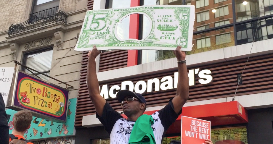 Man holding large $15 bill in front of McDonald's in NYC, Fight for $15 Protest Tax Day 2015