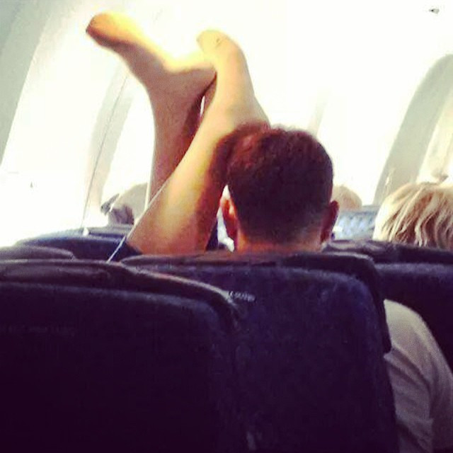 Passenger Shaming, girl laying on airplane with feet up, shoes off, on boyfriend's head