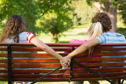 Man secretly holding hands with mistress while cuddling with his girlfriend on a park banch