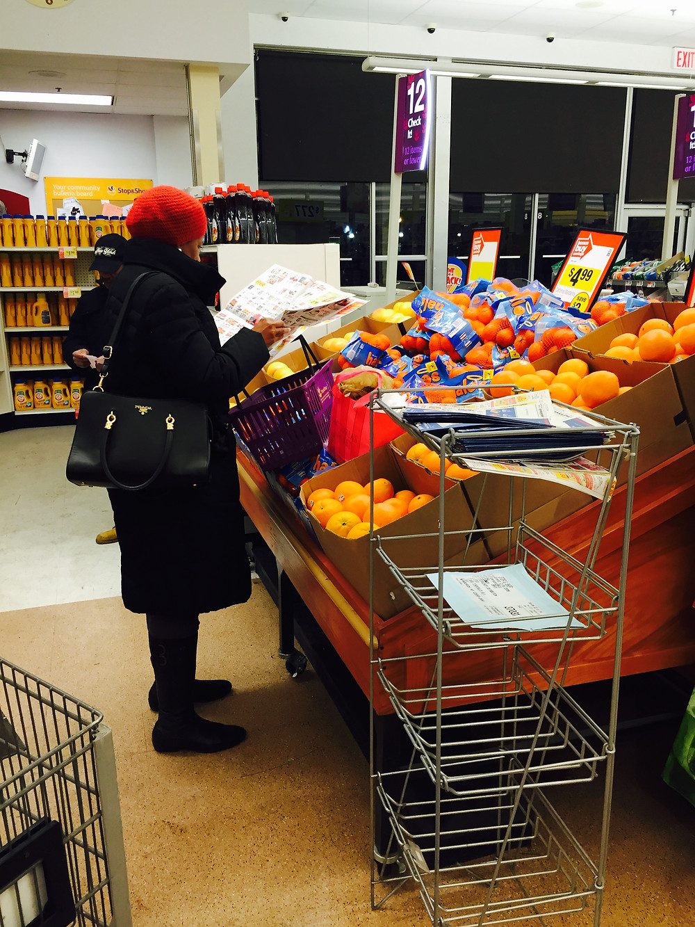 Woman crushing fruit with her basket  in produce section of grocery store as she reads a paper