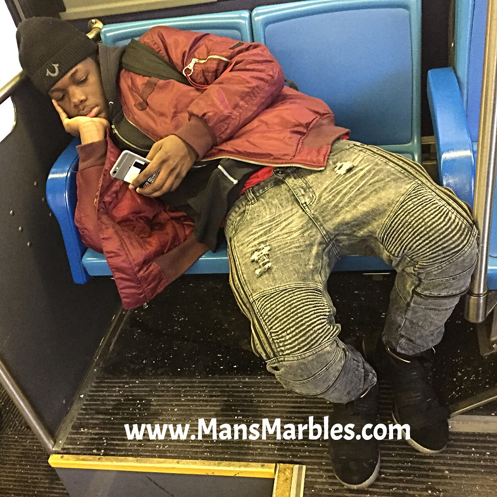 Kid manspreading laying down while checking iphone on NYC bus seats