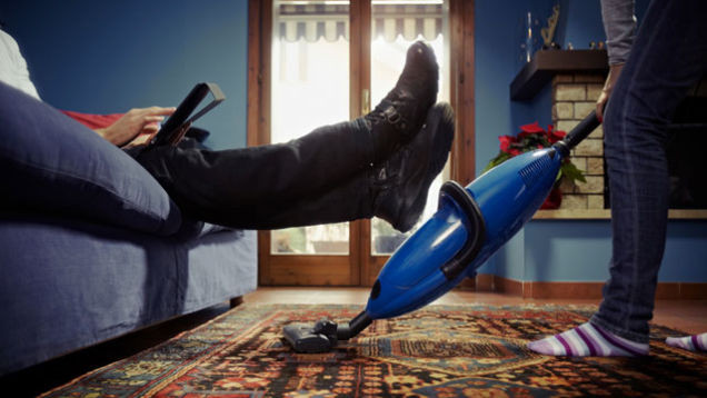 Man relaxing on couch while lifting feet up for wife to vacuum underneath them