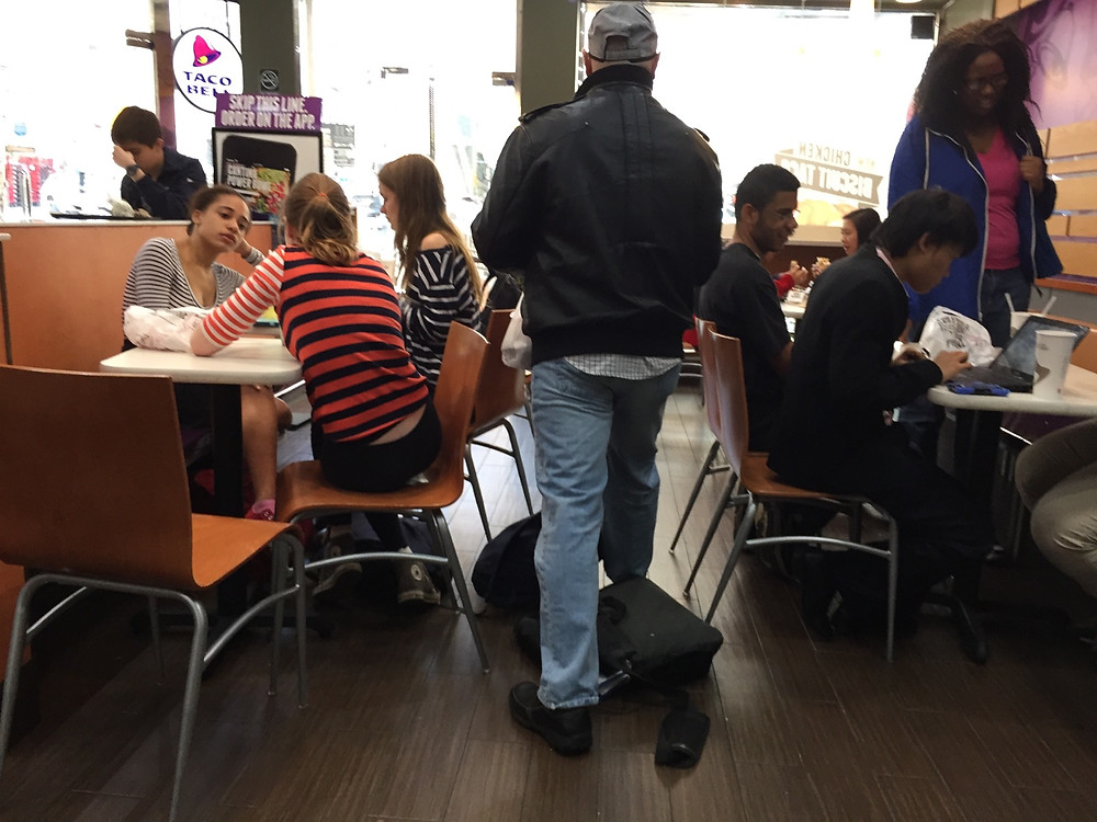 Students bagpreading on the floor in Taco Bell, forces man to step over them #1