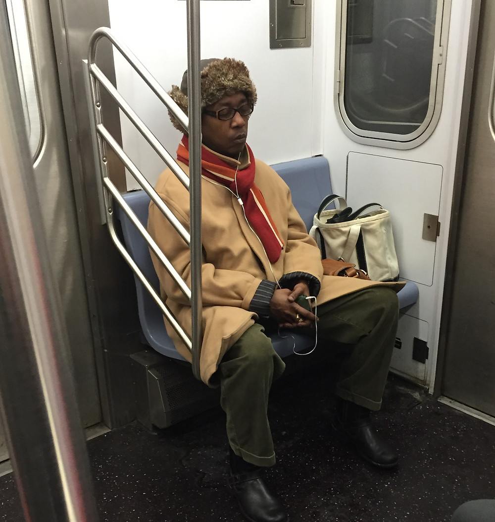 Woman hogging a seater on the 4 train in NYC, bagspreading