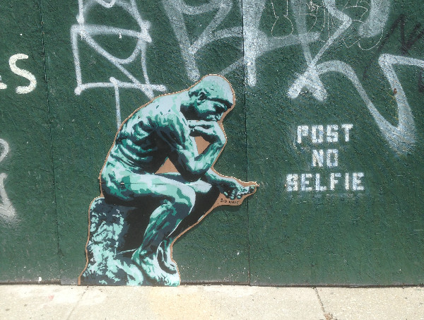 """Thinking man art posted on on nyc construstion wall with """"post no selfie' spray painted next to it"""