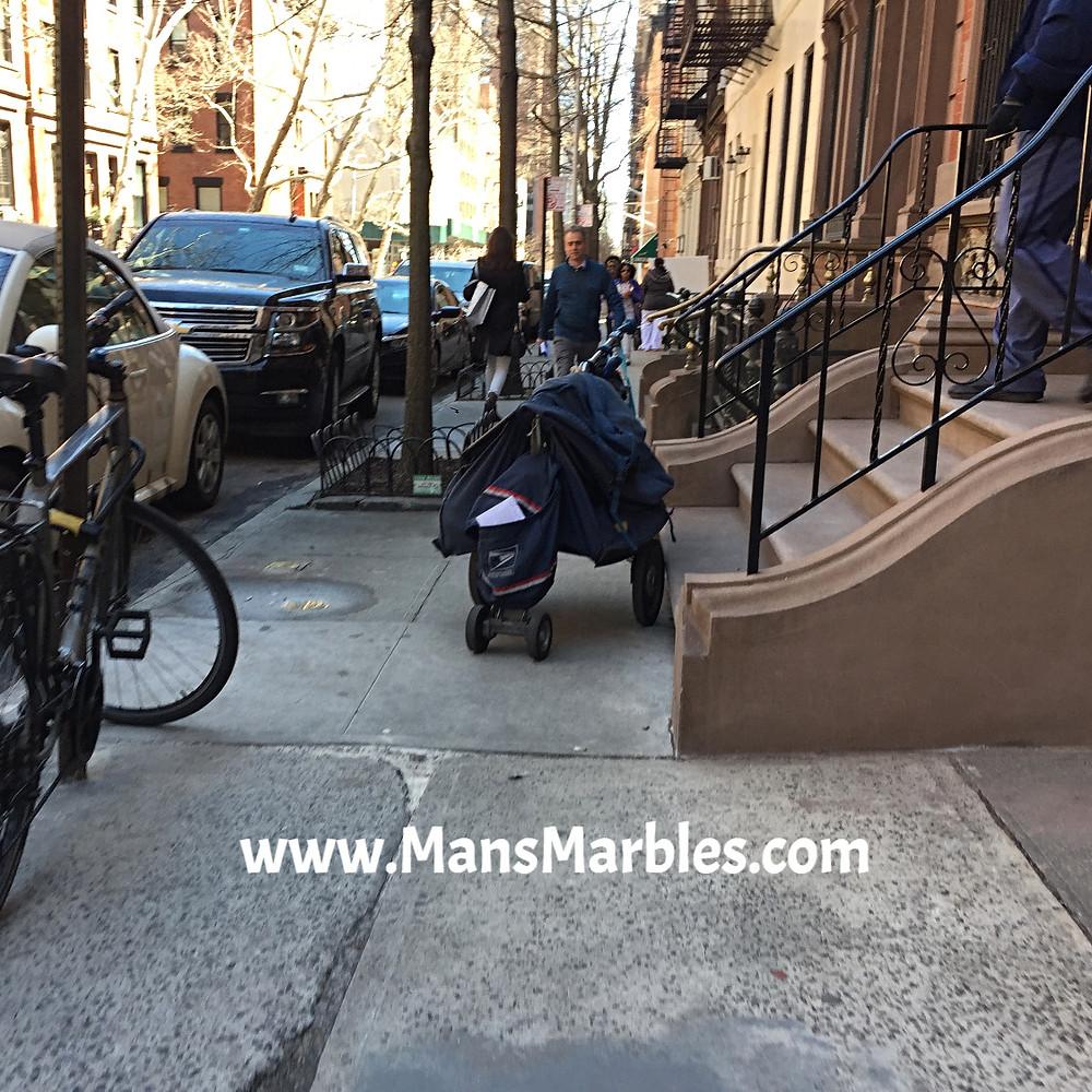 Mailman blocking sidewalk with mail bag