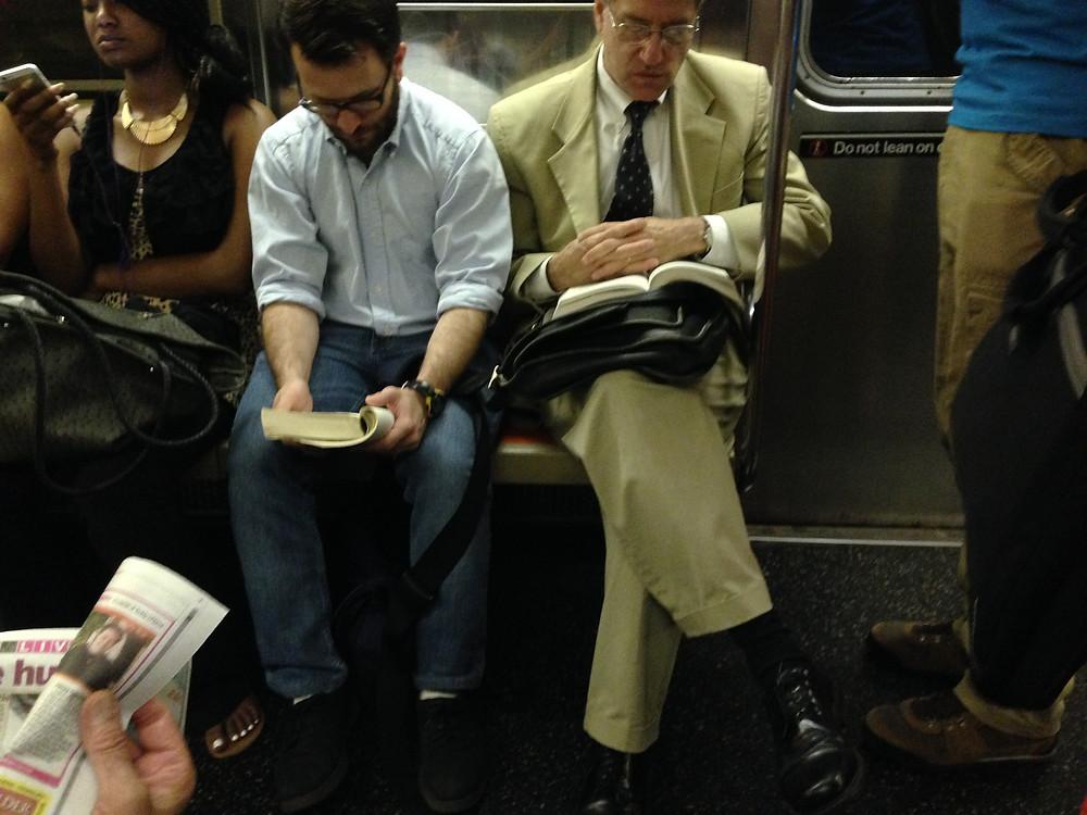 Man blocks train aisle by crossing his legs like a woman, tripping hazard