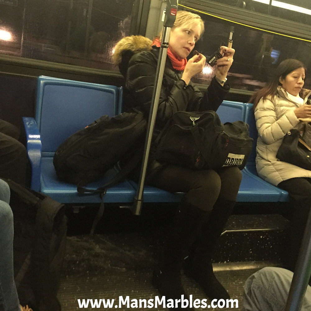 woman making weird faces doing makeup hogging seats nyc bus