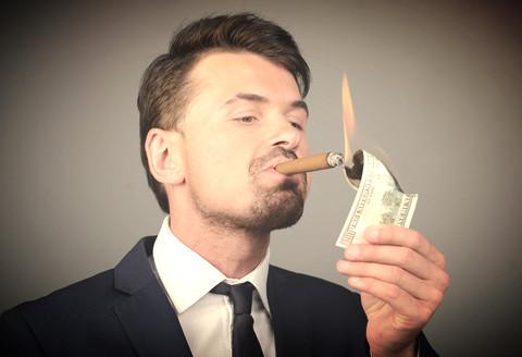 Smug business man lighting his cigar from a burning hundred dollar bill