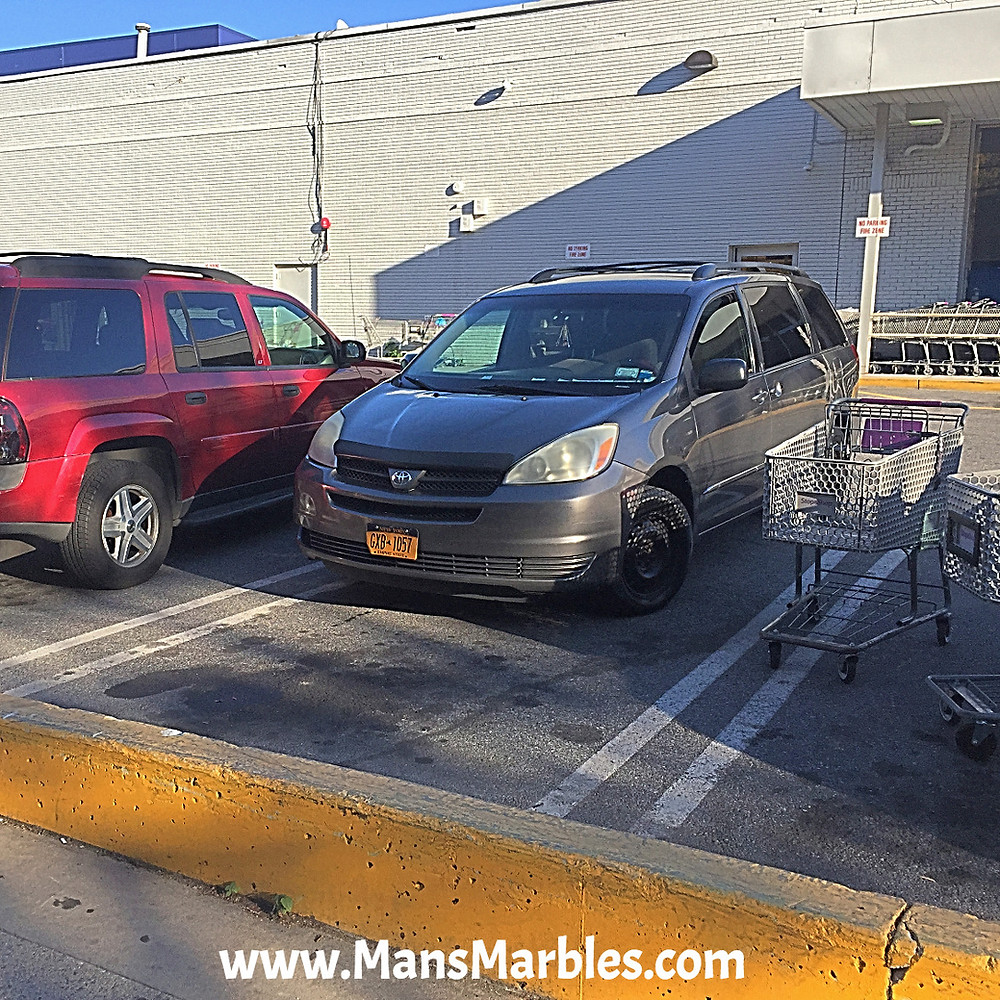 Parking fail dominoes, car parked half way into parking spot because shopping carts block another spot