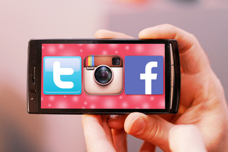 Hand holding a snert phone with social networking icons for facebook, instagram, and twitter