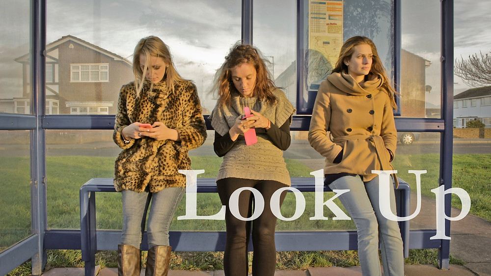 Look Up film image og 2 girls staring at their cell phones while one is looking at the world around her