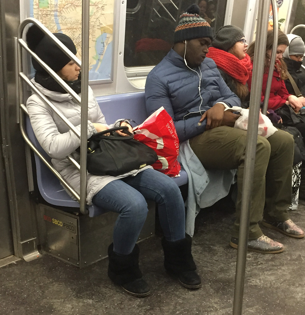 A big man being considereate by not manspreading next to inconsiderate woman bagspreading