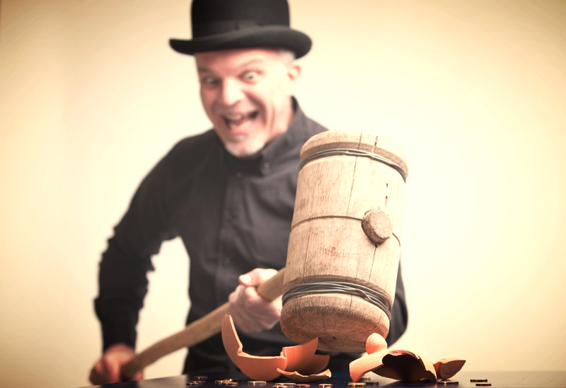 MadMan Sledge Sculpting (smashing) a piggy bank with a wooden mallet