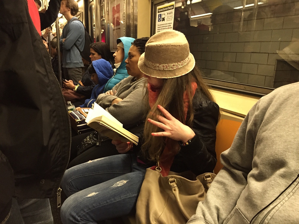reading a book while womanspreading on a packed NYC train #5