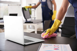 Janitor wiping table in office.jpg