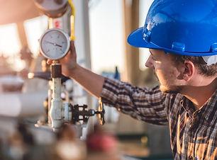 Man checking manometer in natural gas fa