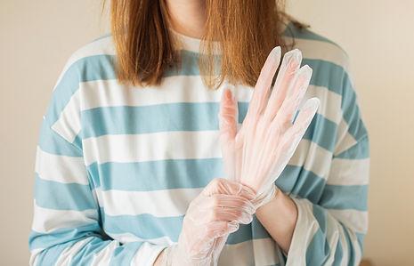 Woman putting on transparent vinyl glove