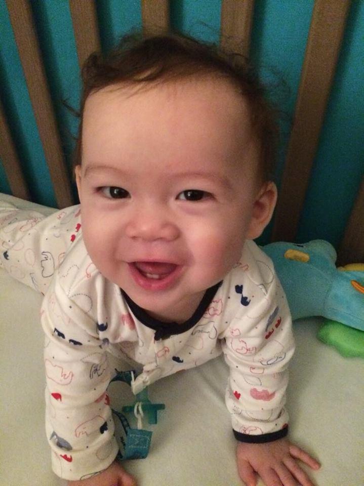 Sebastian smiling in his cot.