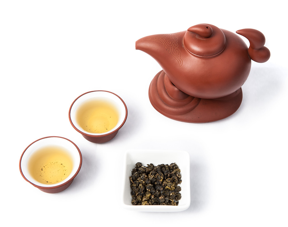 Teapot, two cups and a small bowl of oolong tea.