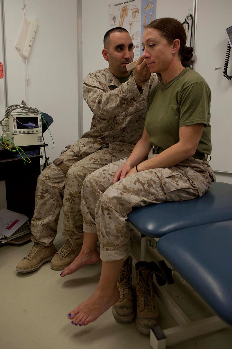 Le lieutenant de la Marine, Orlando Cabrera (à gauche), utilise un capteur pour localiser un point d'acupuncture sur l'oreille d'un patient dans une infirmerie du Camp Leatherneck, province de Helmand, Afghanistan, le 13 décembre 2013. Orlando Cabrera, médecin et acupuncteur, utilise habituellement l'acupuncture pour traiter les membres du personnel ayant des problèmes physiques ou émotionnels.